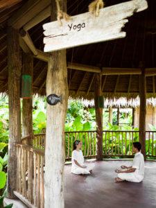 Uma mulher medita com um instrutor no Pavilhão de Yoga do Spa em Six Senses Hideaway Yao Noi. Tailândia.