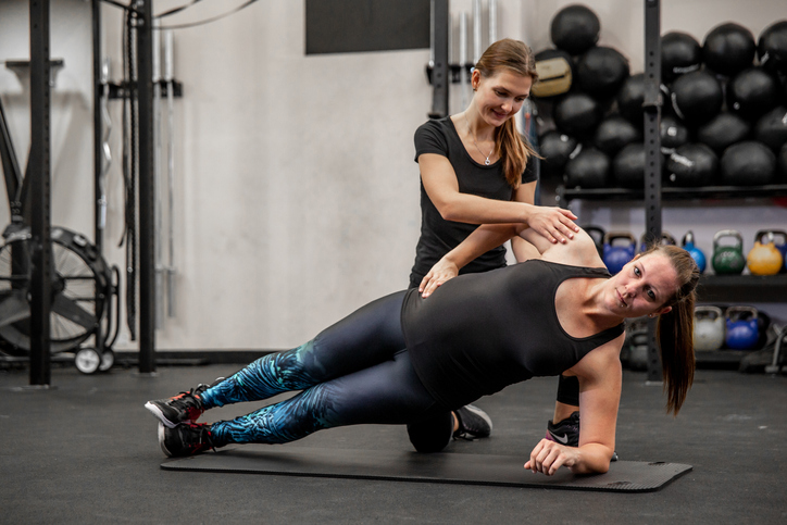 pregnant woman performing side planks with her trainer adding corrections