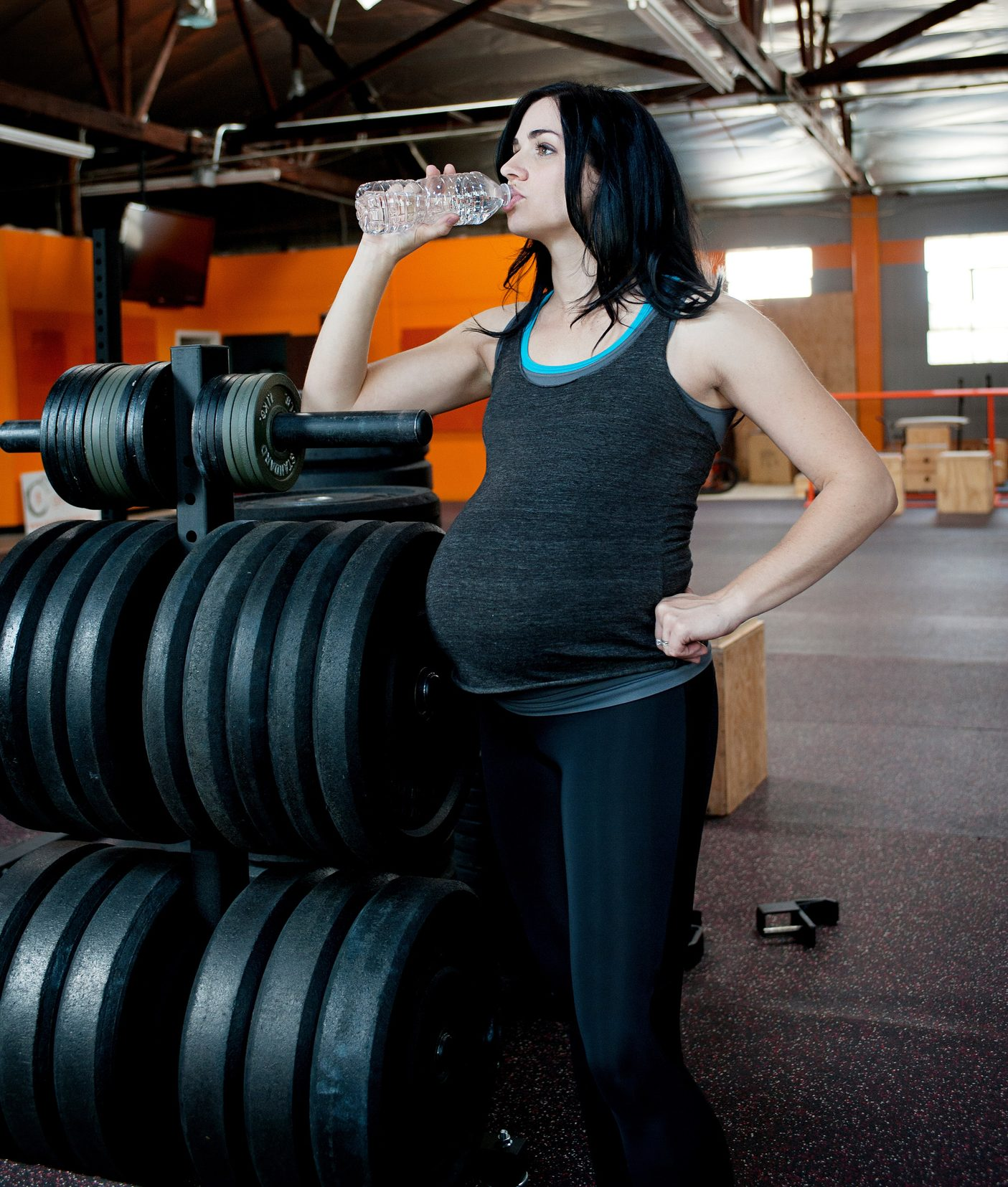 pregnant woman drinking water next to a rack of barbell plates